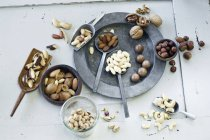 Various nuts on plate and spoons over white wooden surface — Stock Photo