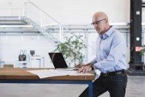 Mann mit Laptop mit Plan auf Tisch — Stockfoto