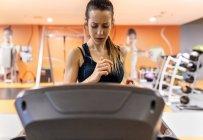 Woman training in gym on treadmill — Photo de stock