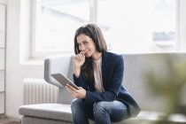 Businesswoman with tablet on couch — Stock Photo