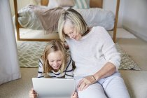 Girl and grandmother using tablet at home — Stock Photo
