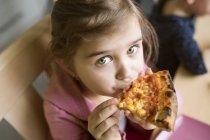 Portrait of little girl eating pizza — Stock Photo