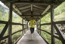 Homem correndo na ponte de madeira — Fotografia de Stock