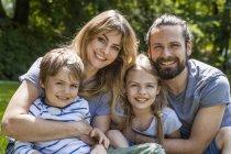 Família feliz sentado ao ar livre — Fotografia de Stock