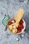Espaguetis, tomates y bulbos de ajo en colador - foto de stock