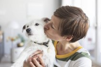 Woman kissing dog — Stock Photo