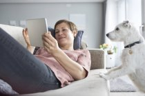 Woman lying on couch using tablet — Stock Photo
