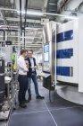 Hommes qui se trouvaient près de machine en usine — Photo de stock