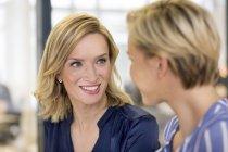 Businesswomen smiling havig discussion — Stock Photo