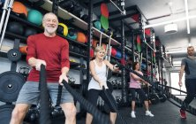 Seniors working out with battle ropes — Stock Photo