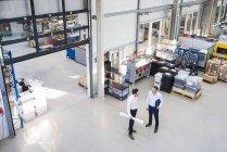 Businessmen talking in factory — Stock Photo