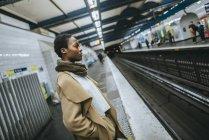Женщина ждет на платформе станции метро — стоковое фото