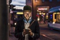 Uomo in città a controllare il cellulare — Foto stock