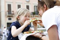 Mother and little daughter eating pizza — Stock Photo