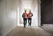 Men walking in building under construction — Stock Photo