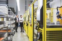Empresários que observam robô industrial — Fotografia de Stock