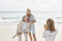 Girl taking pictures of mother and grandmother — Stock Photo