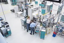 Men talking in factory — Stock Photo