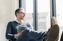 Empresario con tablet sentado con los pies - foto de stock