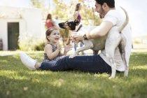 Homme avec la fille et le chien dans le jardin — Photo de stock