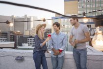 Friends talking on rooftop party — Stock Photo