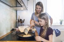 Mother and daughter baking pancakes in kitchen — Stock Photo