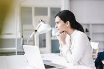 Бизнес-леди с ноутбуком в таблице мышления — стоковое фото