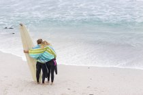 Couple on the beach with surfboard — Stock Photo