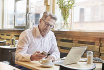 Businessman using smartphone at cafe — Stock Photo