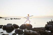 Man doing yoga exercise on rock — Stock Photo