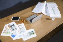 Mesa com fotografias de computador portátil e um esquema — Fotografia de Stock