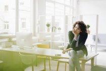 Geschäftsfrau im Büro am Schreibtisch sitzen — Stockfoto