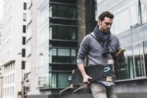 Man carrying skateboard — Stock Photo