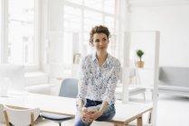 Businesswoman in office sitting on desk — Stock Photo