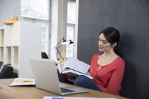 Woman sitting with notebook and laptop — Stock Photo