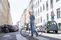 Homme avec vélo traversant la rue — Photo de stock