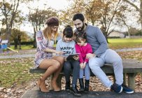 Famille assis sur un banc en regardant tablet — Photo de stock
