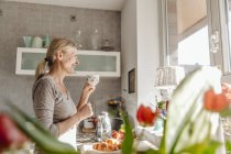 Woman in kitchen looking out of window — Stock Photo