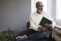 Mature homme lecture livre près de fenêtre — Photo de stock