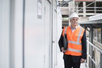 Man walking with documents on construction site — Stock Photo