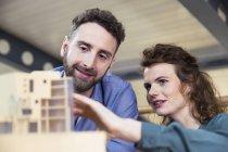 Мужчина и женщина обсуждают архитектурную модель — стоковое фото