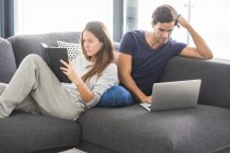 Couple on couch relaxing with book and laptop — Stock Photo