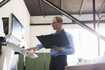 Man with clipboard operating machine — Stock Photo