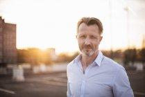 Empresário de pé ao pôr do sol — Fotografia de Stock