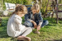 Woman and girl with tortoise in garden — Stock Photo