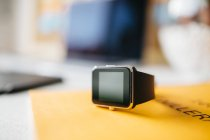 Smartwatch on yellow notebook — Stock Photo