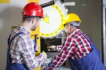 Two men in factory working at CNC machine — Stock Photo
