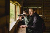 Мальчик и отец с биноклем — стоковое фото