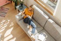 Mujer sentada en un sofá con teléfono celular - foto de stock