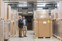 Two men standing in factory warehouse — Stock Photo